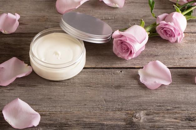 Kosmetische creme mit rosa rosen auf altem holztisch
