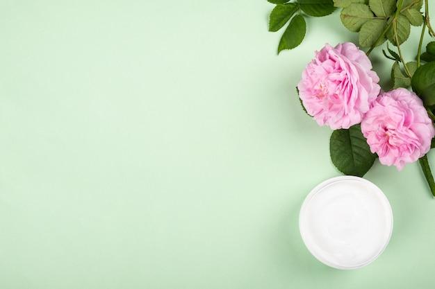Kosmetische creme mit rosenduftschönheitshautpflege flach mit kopienraum auf grünem hintergrund