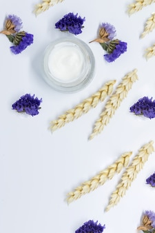 Kosmetische creme mit weizen auf weißem hintergrund