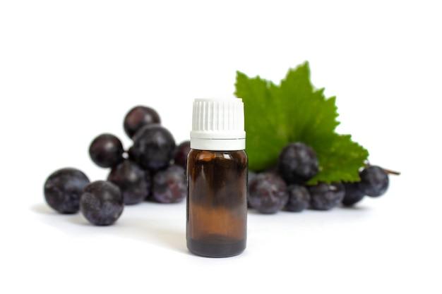 Kosmetische flasche und purpurrote trauben auf weißem hintergrundkosmetik