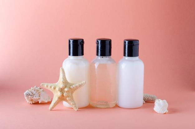 Kosmetische flaschen auf einem hintergrund mit farbe der phasenkoralle. zusammensetzung von shampoo-, conditioner- und bodylotionsflaschen.
