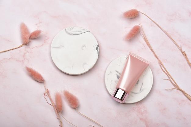 Kosmetische flaschenbehälter auf rosa marmorhintergrund