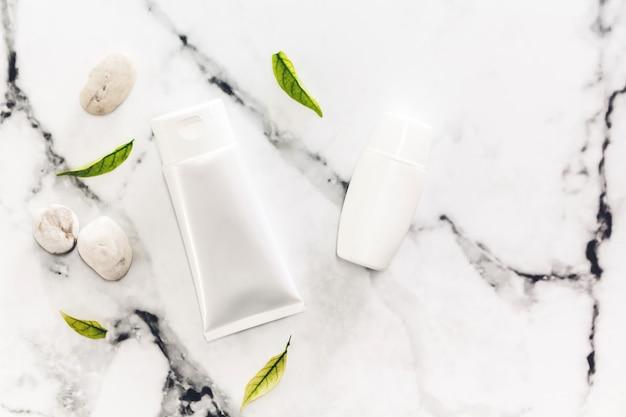 Kosmetische flaschenhautpflegeprodukte mit badekurortsteinen und -blättern auf weißem marmorhintergrund.