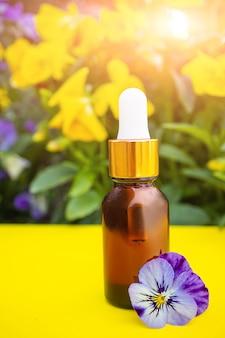 Kosmetische glasflasche mit einer pipette auf dem platz eines busches mit bratschenblüten. konzept für natürliche bio-kosmetik, öle, aromatherapie, spa, öko, bio.