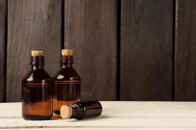 Kosmetische glasflasche mit korkstopfen. braune flaschen auf weißem tisch gegen dunkle holzwand