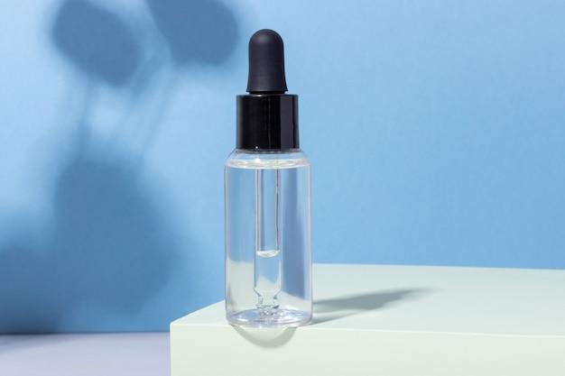 Kosmetische glasflasche mit tropfer auf podium mit harten schatten.
