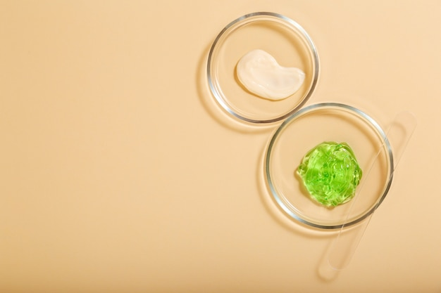 Kosmetische hautpflegeprodukte in petrischalen auf beigem hintergrund. aloe-gel, feuchtigkeitscreme-naturkosmetik für die kosmetologie in laborglaswaren. flache lage mit kopienraum.