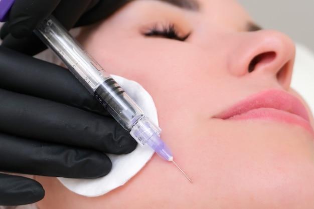 Kosmetische injektionen zur hautverjüngung. die kosmetikerin injiziert einer jungen frau eine spritze in die haut.