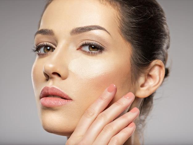 Kosmetische make-up tonale grundlage ist auf dem gesicht der frau. hautpflegekonzept.