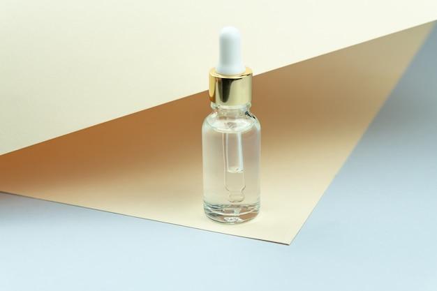 Kosmetische ölflasche mit pipettentropfer, der auf hellbraunem hintergrund steht. hautpflegekonzept. naturkosmetik. moderner schönheitstrend.