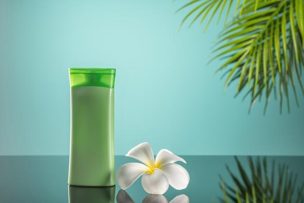 Kosmetische produktanzeigen auf grünem klarem hintergrund mit plumeria-blume und grünem blatt