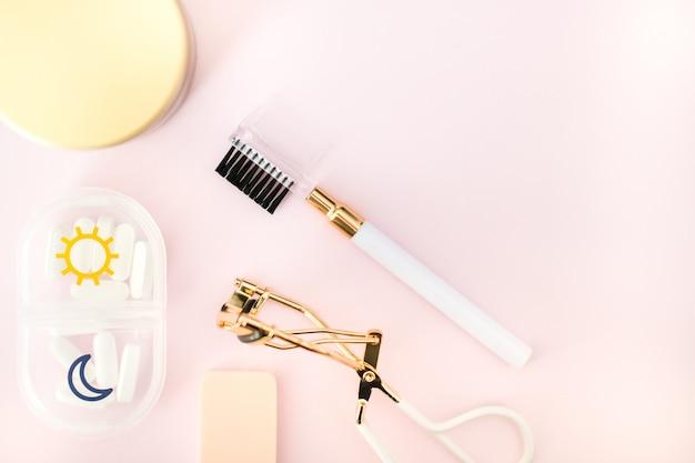 Kosmetische produkte, brauen-kamm und wimperlockenwickler und pillenkasten auf rosa hintergrund. beauty-konzept.