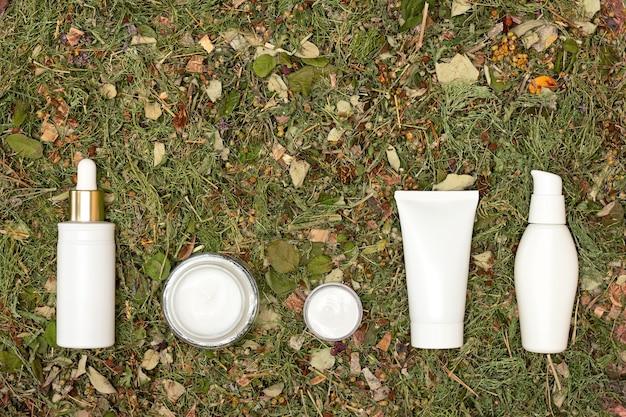 Kosmetische produkte für die gesichtshautpflege auf grünen kräutern natürliche gesichtspflegekosmetik textfreiraum