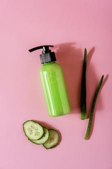 Kosmetische produkte mit aloe vera und gurke auf rosafarbenem hintergrund. platz für text. flache zusammensetzung