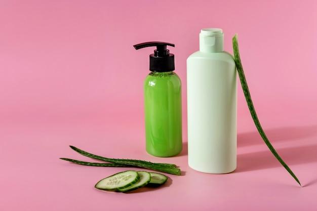 Kosmetische produkte mit aloe vera und gurke auf rosafarbenem hintergrund. platz für text.