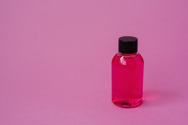 Kosmetische produktflasche für körperhautpflegekosmetik oder -haar auf rosa hintergrund. seitenansicht mit exemplarplatz, fahne oder schablone. das konzept des schönheitsprodukts. leeres etikett für das branding-layout.
