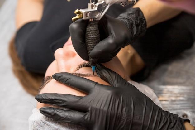 Kosmetische verfahren zur behandlung von augenbrauen. microblading im schönheitssalon. professionelle kosmetologie. der vorgang des aufbringens des pigments, formen der augenbrauen. permanente make-up-augenbrauen, tätowieren