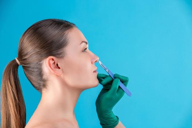 Kosmetischer chirurg, der klientin im büro untersucht. arzt überprüft das gesicht der frau, die nase vor der plastischen chirurgie. hände des chirurgen oder der kosmetikerin berühren frauengesicht. nasenkorrektur