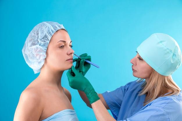 Kosmetischer chirurg, der weiblichen kunden im büro überprüft.