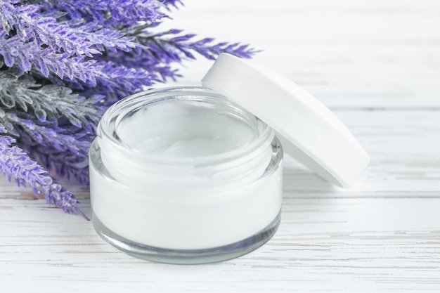 Kosmetischer cremebehälter auf weißem hölzernem hintergrund mit blumen