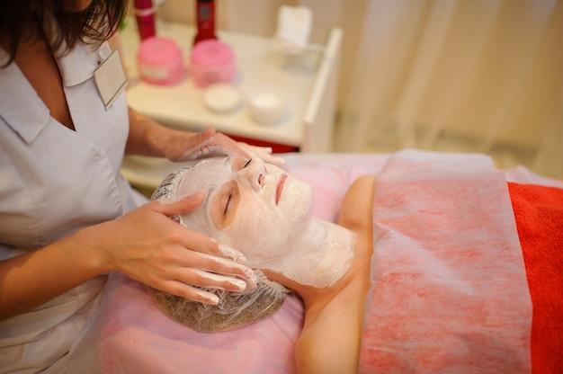 Kosmetischer eingriff mit einer weißen maske auf einer jungen weiblichen gesichtsnahaufnahme.