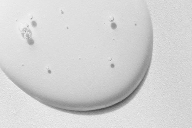 Kosmetischer geltropfen auf weißer strukturierter oberfläche