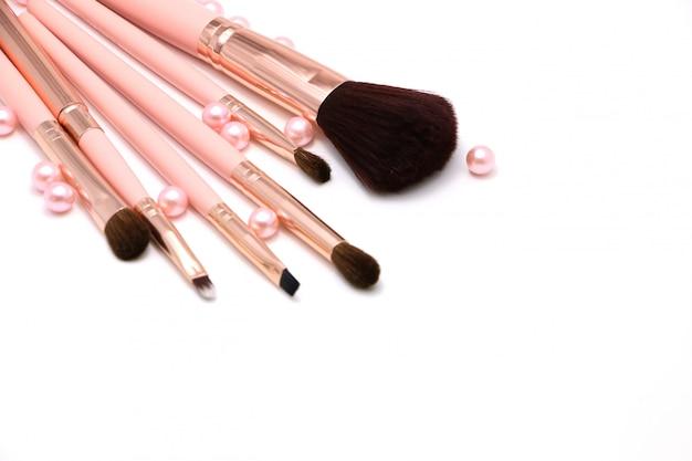 Kosmetischer satz von bilden bürste auf der rosa und perlenebene, die auf einem weißen hintergrund lokalisiert wird
