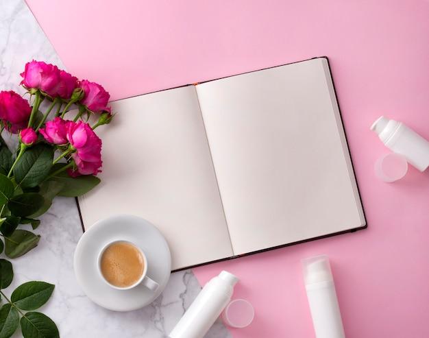 Kosmetisches hautpflegeprodukt, offenes notizbuch, kaffee und blumen auf rosa