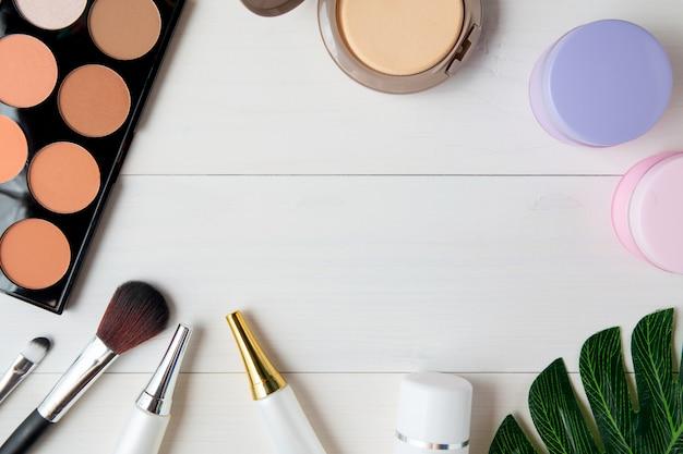 Kosmetisches make-up und hautpflegeprodukt und blätter auf weißer hölzerner tabelle