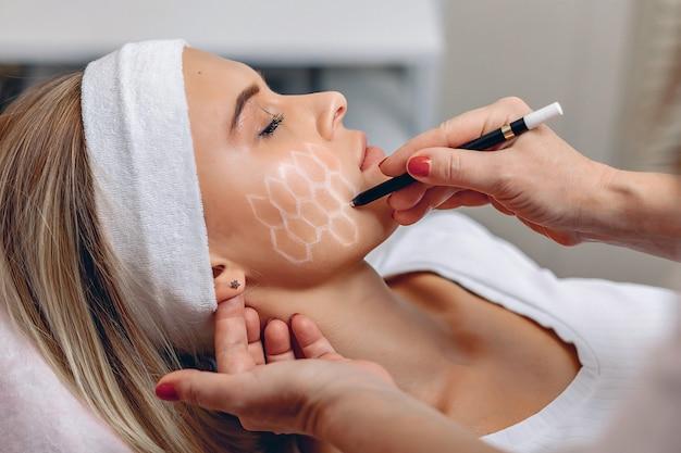 Kosmetisches netz im gesicht des kunden. meisterkosmetikerin bereitet einen kunden auf akupunktur vor.