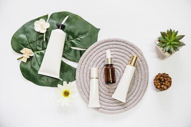 Kosmetisches produkt des badekurortes auf seil-untersetzer mit blume; blatt; pinecone und kaktuspflanze über weißem hintergrund