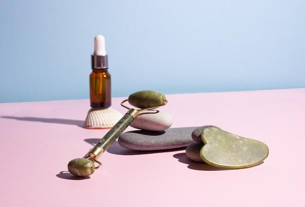 Kosmetisches produkt in einer glasflasche mit einer pipette und einem guasha e-schaber und einer rolle. glatte steine in der nähe. das konzept der hautpflege, kosmetik.