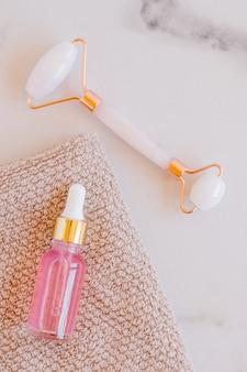 Kosmetisches rosenöl und rosenquarz-gesichtsmassagegerät gua-sha-stein für die gesichtsmassage zu hause. hautpflege- und gesichtsbehandlungskonzept.