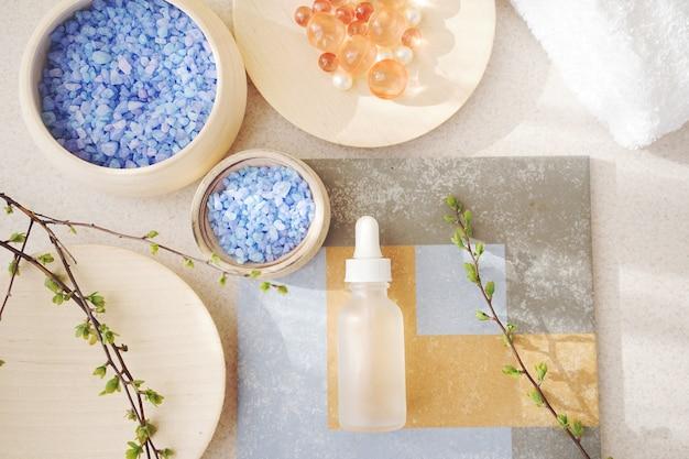 Kosmetisches serum und meersalz in holzschalen. spa-konzept