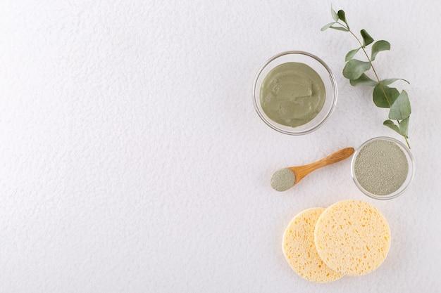 Kosmetisches tonpulver für haut und haar, spa und wellness, naturkosmetik, schwämme und bürsten auf weißem hintergrund mit kopierraum