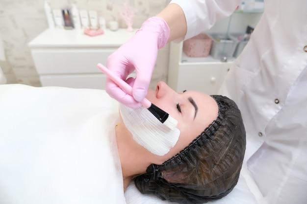 Kosmetologie. schließen sie herauf bild der reizenden jungen frau mit geschlossenen augen, die gesichtsreinigungsverfahren im schönheitssalon erhalten.