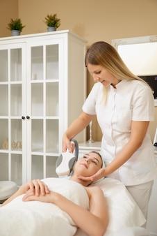 Kosmetologie. schöne frau, die laser-haarentfernungsverfahren am schönheitssalon erhält. kosmetikerin hände, die schönheitsbehandlung für weibliches gesicht am spa-salon tun.