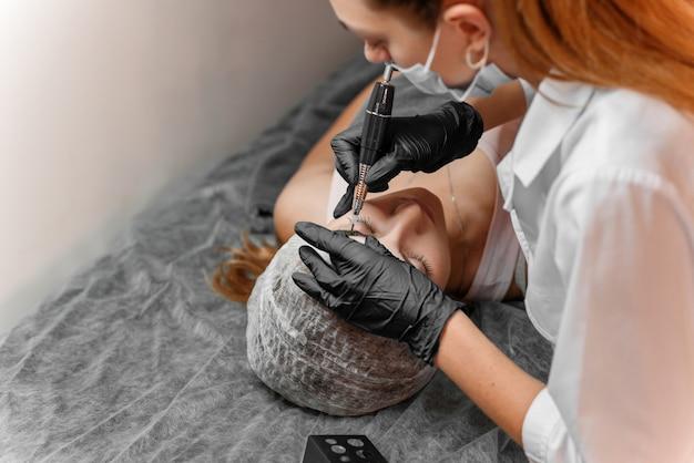 Kosmetologische behandlung. berufskosmetiker, der augenbrauentätowierung am frauengesicht tut. permanentes brauenmake-up im schönheitssalon, abschluss oben.