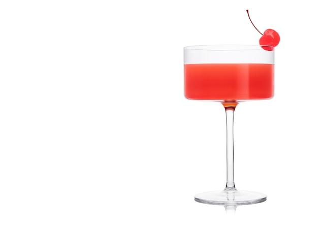 Kosmopolitischer cocktail in modernem kristallglas mit rosa kirsche auf weißem hintergrund. platz für text