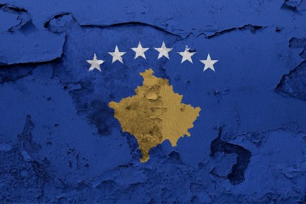 Kosovo-flagge gemalt auf der gebrochenen betonmauer