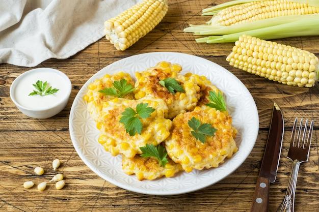 Koteletts von den körnern des in büchsen konservierten mais mit petersilie auf einer platte.