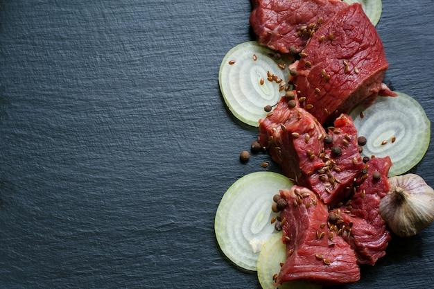 Koteletts von rohem kalbfleisch mit zwiebelringen und schwarzem pfeffer