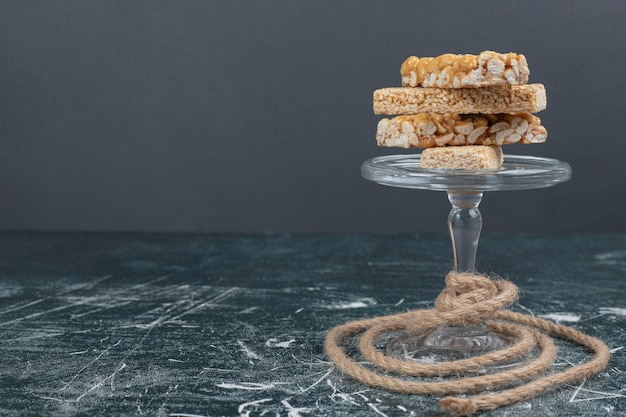 Kozinaki süßigkeiten mit samen und nüssen auf glasplatte mit seil. hochwertiges foto