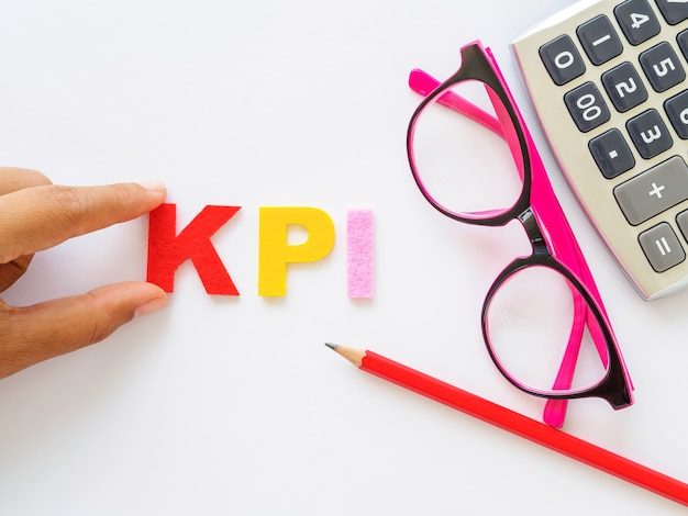 Kpi-alphabet mit rotem bleistift und rosa gläsern setzte an weißen tabellenhintergrund