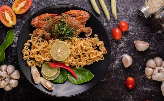 Krabben tom yum mama mit zitrone, chili, tomate, knoblauch, zitronengras, kaffernlimettenblättern auf dem teller