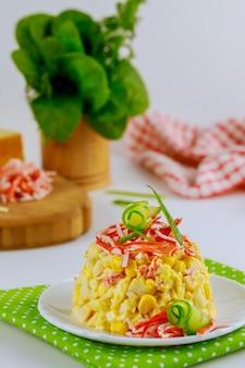 Krabbenfleischsalat mit zuckermais, käse und eiern, dekoriert mit corn chips und gurken. vertikales foto.