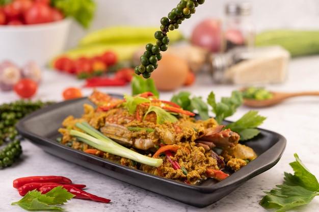 Krabbengebratenes currypulver auf einem schwarzen teller auf dem zementboden.