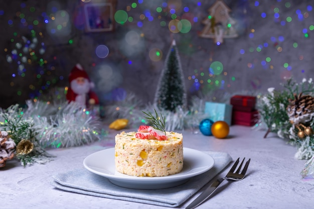 Krabbensalat mit mais und eiern auf einem weißen teller. neujahr und weihnachten. traditioneller russischer salat