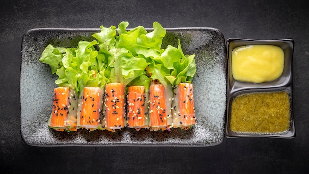 Krabbenstäbchen-salatrolle mit bio-gemüse, sesam oben und salatdressing in keramikplatte auf dunklem texturhintergrund, draufsicht, gesundes essen