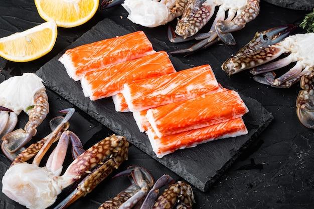 Krabbenstangen halbfertiges fischhackfleisch der meeresfrüchte mit blauem schwimmkrabbensatz, auf schwarzem hintergrund